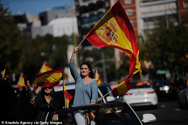 Supporters of the right-wing Vox party wave Spanish flags in protest in the capital on Monday.