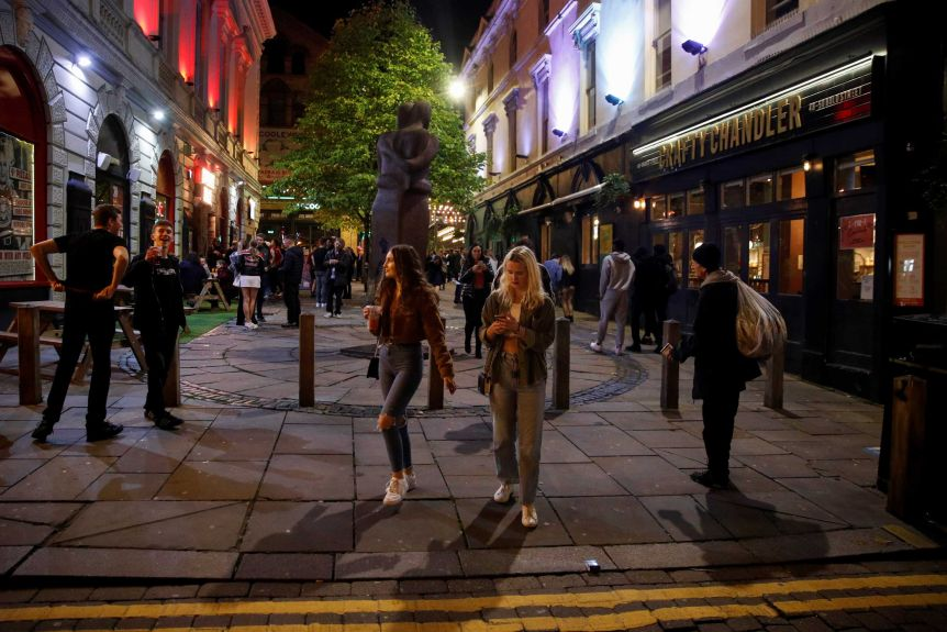 People walk at night in a square in Liverpool, England.