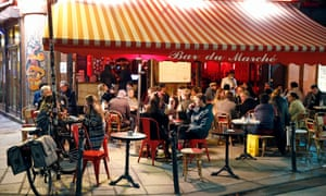 People enjoy a drink on the terrace of a hotel as French President Emmanuel Macron uses a curfew order to speed up the corona virus outbreak.