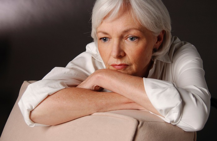 The visible older woman rests her cheek on her folded arms.