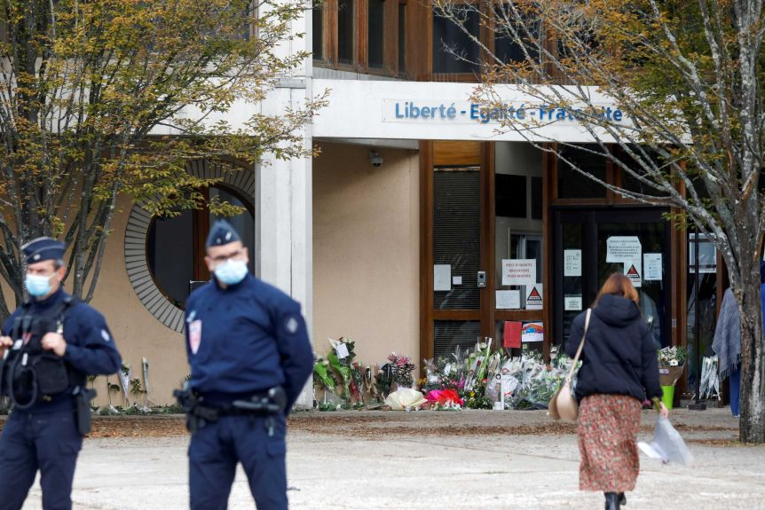 Police stand by as people bring flowers to Boise de Alney College after the attack.