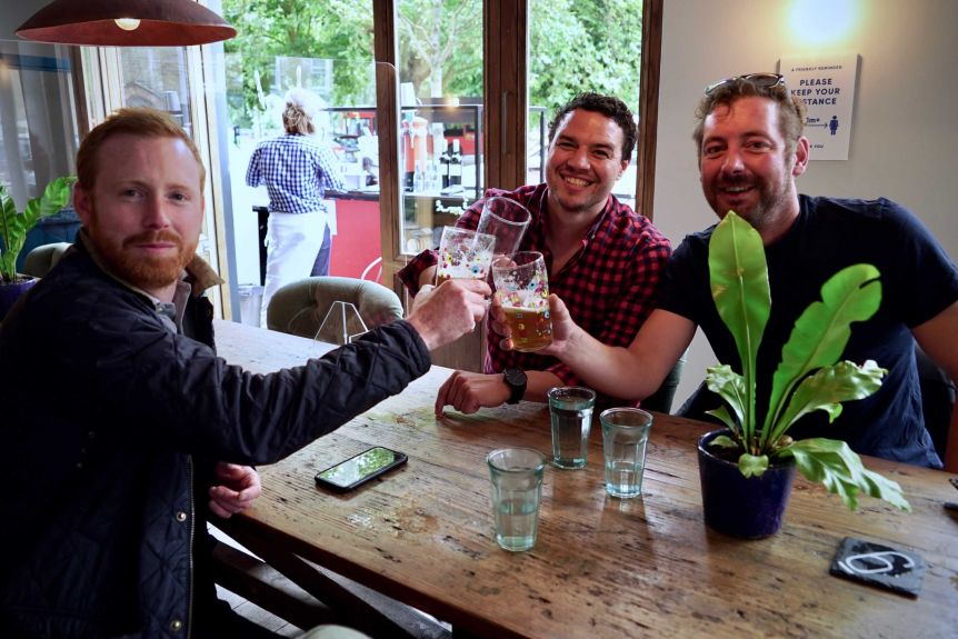 Three men cheer with beer glasses across a bar table.