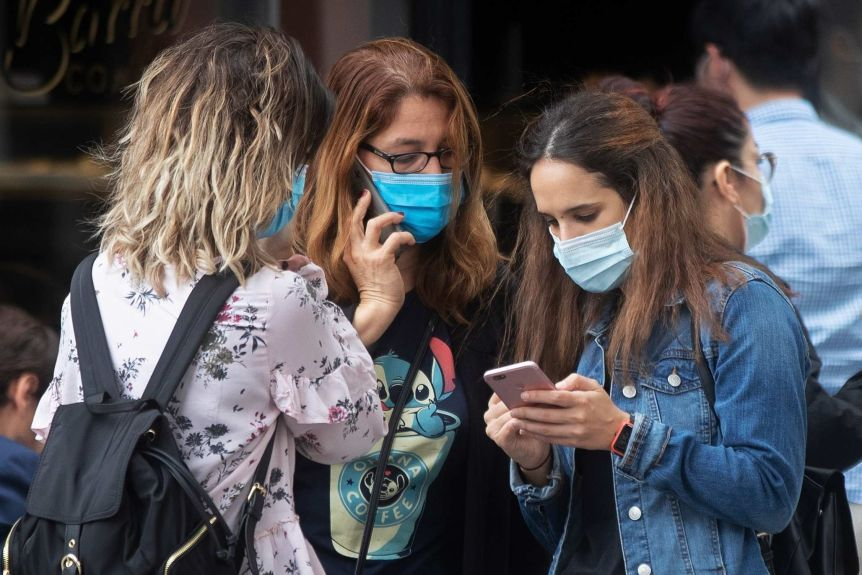 Three young women wearing masks stand together and use their phones