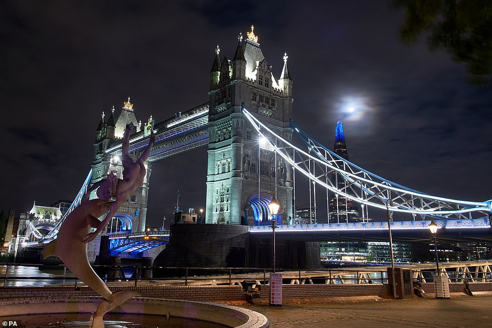 Britain was treated to a spectacular display of the first Halloween Blue Moon in 40 years on Saturday.  Image: Moon visible above Tower Bridge in central London