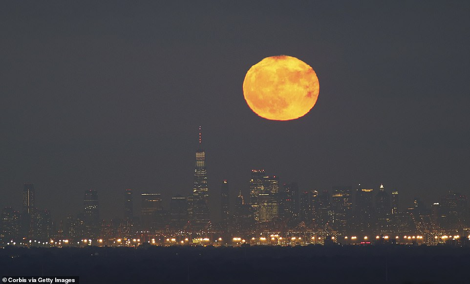 Full Blue Moon and Hunters Moon rises behind Manhattan and a World Trade Center under New York City on Halloween