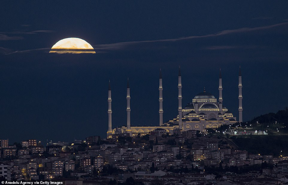 In Istanbul, Turkey, the moon can be seen hanging over the Great Camelia Mosque