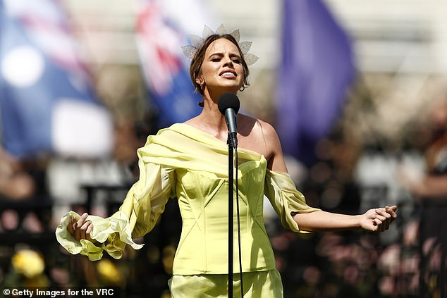 Singing his heart out: the masked singer-winner and neighboring star Bonnie Anderson performed the Australian National Anthem live from Flemington