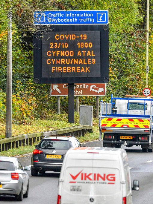 You see an aerial photo of a freeway with a black mark on COVID-19 controls for Welsh and English warning motorists.