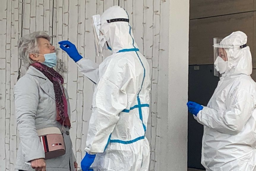 A health worker in full PPE wipes her nose while a woman beats and tilts her head