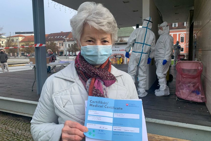An elderly woman with short gray hair in a mask holding a medical certificate