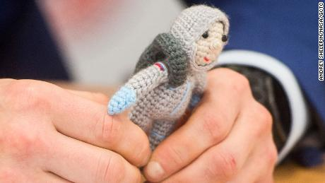 Expedition 64 crew member Sergei Good-Sverkov holds a knitted astronaut named Yuri, made by his wife Olga.