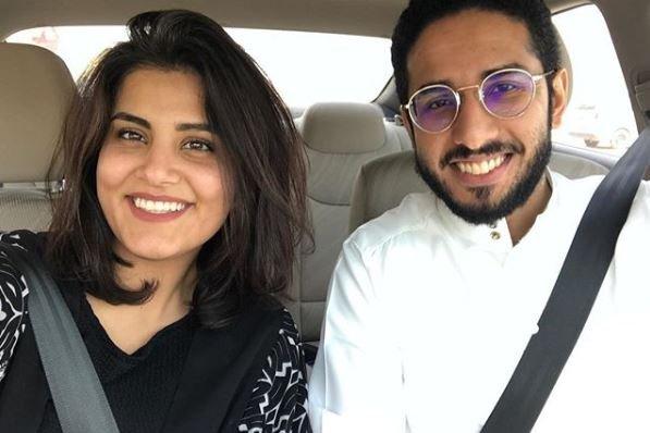 A woman and a man pose in front of a car for a selfie.