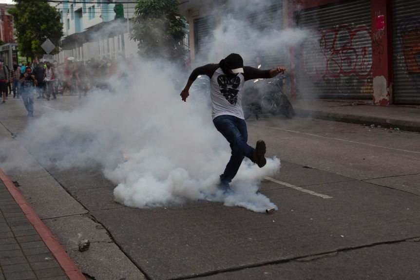 A protester returns a tear gas canister fired by police near a Guatemalan Congress building