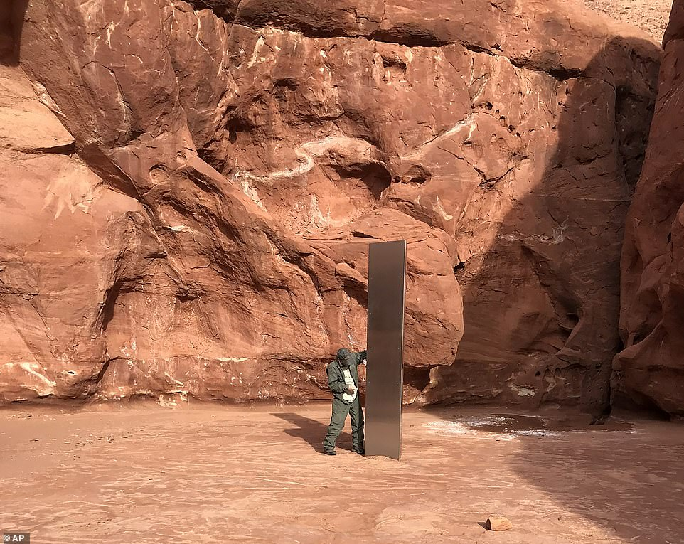 A photo provided by the Utah Department of Public Safety shows a state employee inspecting a mysterious metal monolith installed on the ground in a remote area of the Red Rock Desert earlier this week.
