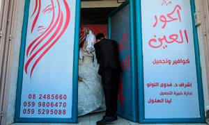 Palestinian groom Ahmed Omar Kalla picks up his hidden bride from a beauty salon in northern Gaza.