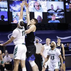 Richard Harvard, 42, of BYU, fired a shot into the Utah Valley's Fardows Imak (11) when the Cooks won 82-60 against the Wolverines at the Marriott Center in Provo on Saturday, November 28, 2020.