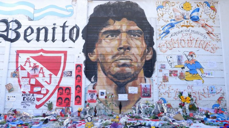 Fans place offerings to late Diego Maradona in front of mural outside Argentinos Juniors' Stadium Diego Maradona
