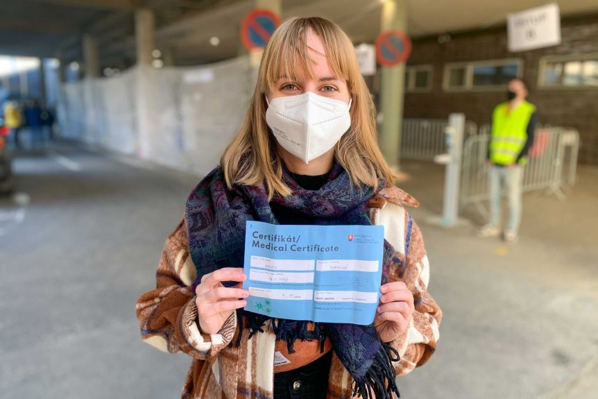 A young woman in the mask holds a medical certificate
