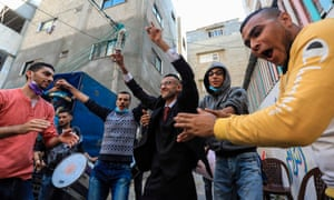 Palestinian groom Mohamed Ahmad Ashor dances with male relatives and friends while waiting for the groom at his wedding amid Gowd-19 epidemic in Gaza City.