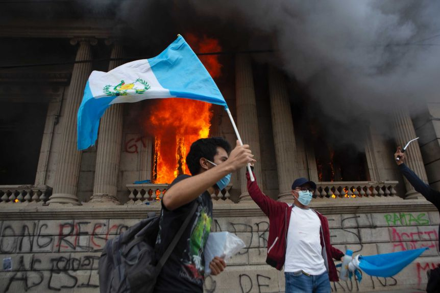 A protester waves the Guatemalan flag as part of a congressional building