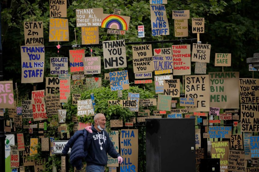 A person wears a mask under his cheek and walks with card signs with the words 'Thank you NHS' and 'Be safe'.