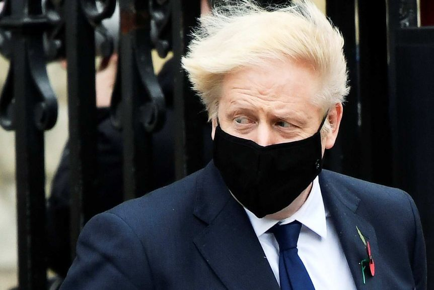 Boris Johnson's hair blows in the wind, and he's wearing a side, black mask.