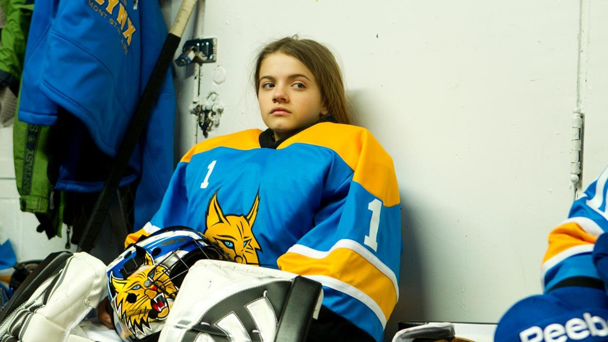 A young woman in goalie gear sitting on a bench.
