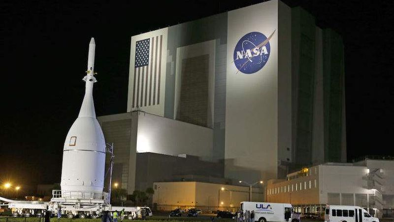 Night view of a white rocket with flag and NASA logo near the majestic building.