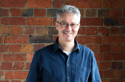 A man in a blue shirt and orange pants stood in front of a red brick wall and smiled slightly.