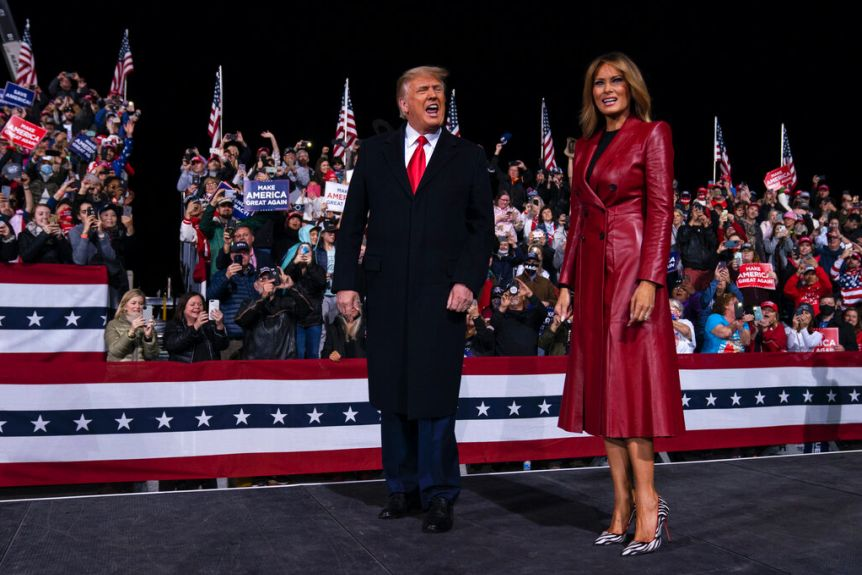 You see Donald Trump and Melania Trump on a rally stage at night.