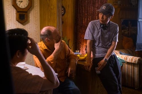 Le réalisateur Lee Isaac Chung (à droite) de «Minari» s'entretient avec les acteurs Will Patton (au centre) et Steven Yeun (à gauche) sur cette photo prise par Melissa Lukenbaugh et fournie par A24. (Archivage et revente interdits)