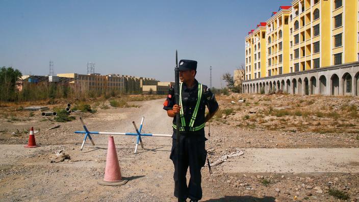 Un policier devant la route menant à ce que Pékin nomme un camp d