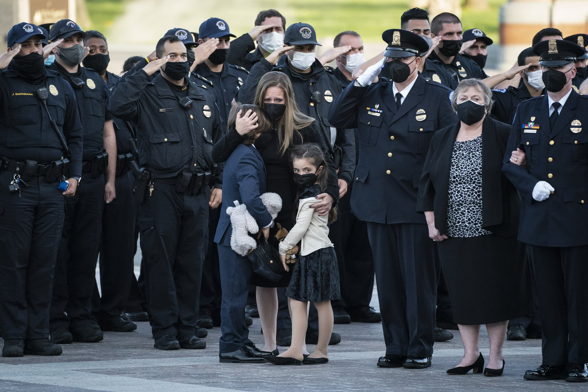 Officer Evans' wife and son and daughter oversee the memorial service.  AP = Yonhop News
