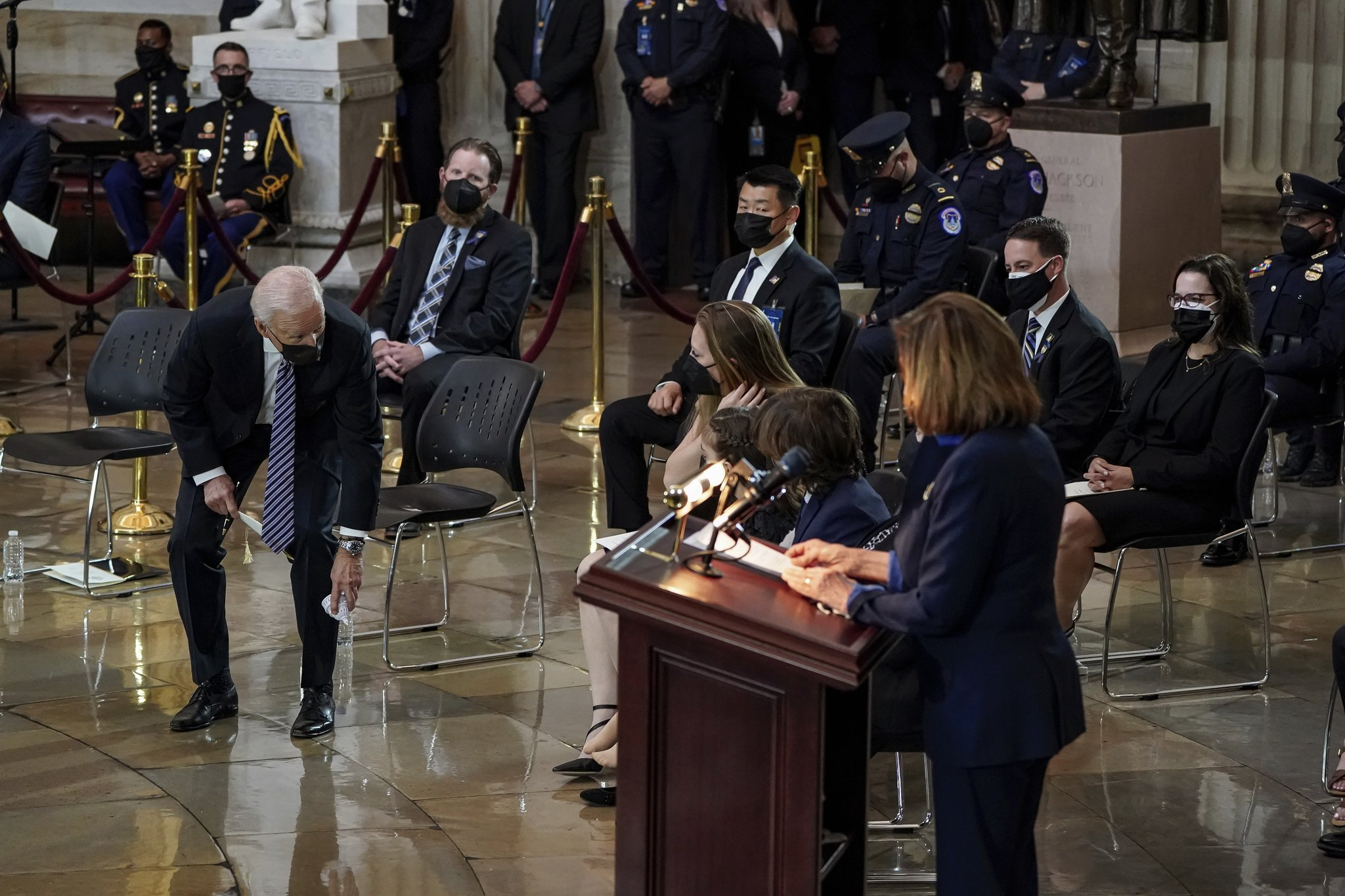 President Biden picks up a Capitol dome-shaped toy that fell to the ground during the commemoration of House Speaker Nancy Pelosi.  AP = Yonhop News