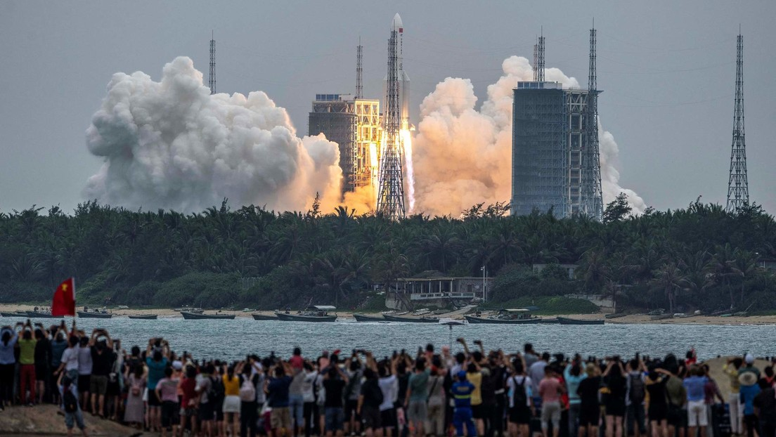 Dozens of people watch from a beach as the Long March-5BY2 rocket launches from the Wenchang Space Launch Center in Hainan, China.  April 29, 2021.