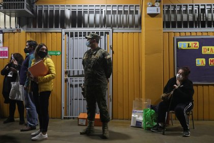 Electoral workers and military personnel are waiting for votes to be saved at the end of election day during elections for governors, mayors, councilors and constituency members to draft a new constitution to change Chile's constitution.