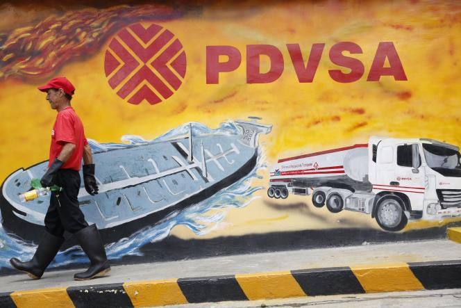 On August 29, 2014 in Caracas, a worker walks past a wall painted with the state-owned Petroleum de Venezuela SA (PTVSA) logo.