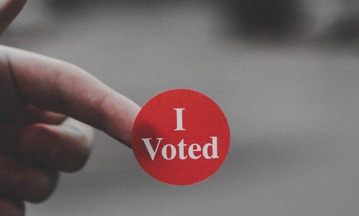 """Zoom sur une main, avec sur l'index une petite gommette rouge """"I voted'"""