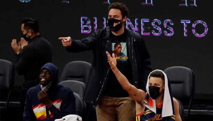 La superstar NBA des Golden State Warriors, Klay Thompson, pointe du doigt ses coéquipiers depuis le banc aux côtés de Draymond Green et Stephen Curry