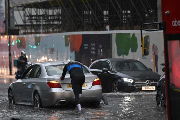 On July 21, 2021, a driver was forced to push his car on flooded London Street in the district of Nine Elms.