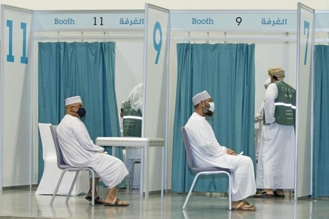 Men are waiting to receive the Covid 19 vaccine on June 23, 2021 in Muscat, the capital of Oman.