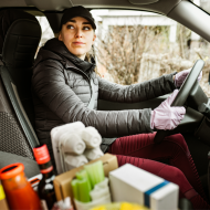 A woman in a car delivering groceries