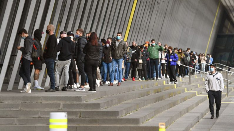 Une longue queue de personnes qui attendent d'être vaccinées à Melbourne.