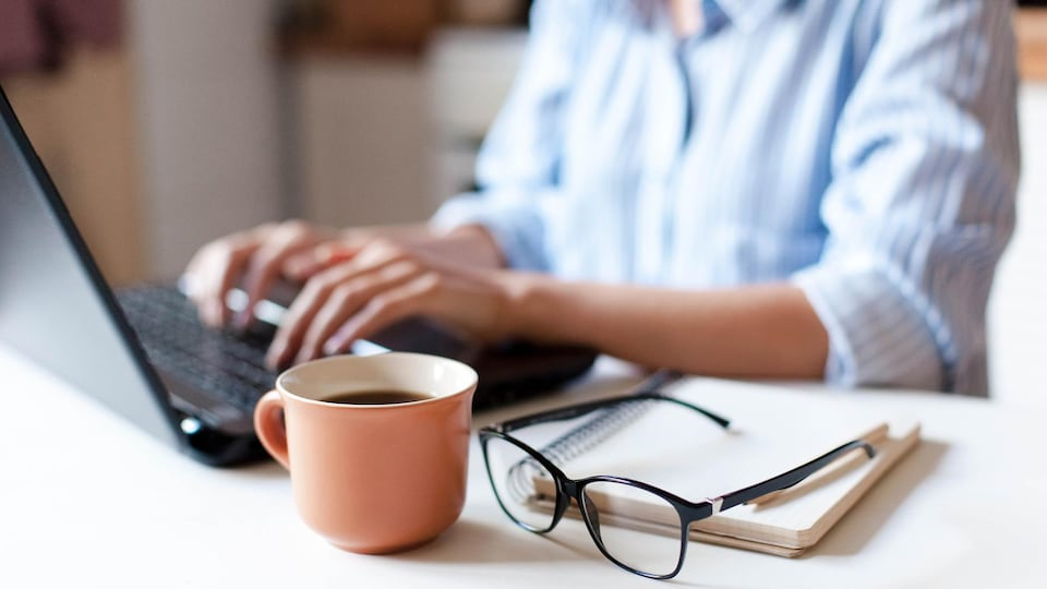 A woman works on a laptop.  A cup of coffee and glasses are on the front.