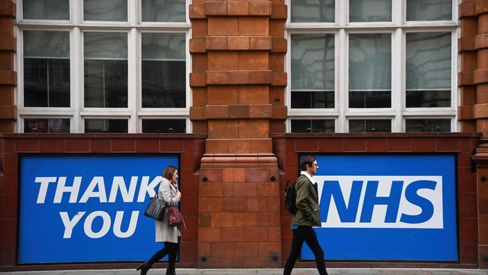 Des passants devant un message «merci NHS», en référence au National Health Service (Service de santé national) britannique, à Manchester, le 5 octobre 2021. for the National Health Service (NHS). Photo d